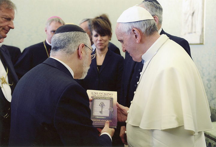 Over the course of his career, Rabbi Goldin has meet with many prominent people. Here, he's with Pope Francis, who is looking at one of Rabbi Goldin's books.