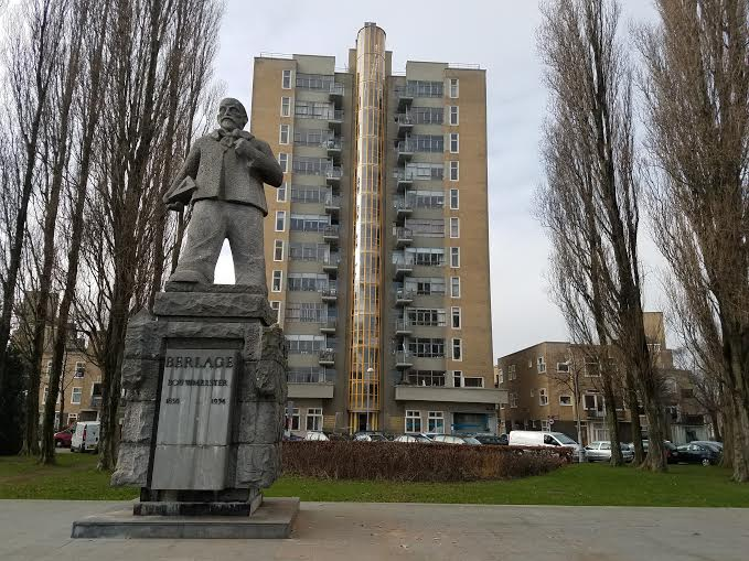 Placed in 1966, a statue of the Dutch architect Berlage stands in front of Amsterdam's first high-rise 'skyscraper,' close to Anne Frank's childhood apartment in the River Quarter, January 2017. (Matt Lebovic/The Times of Israel)