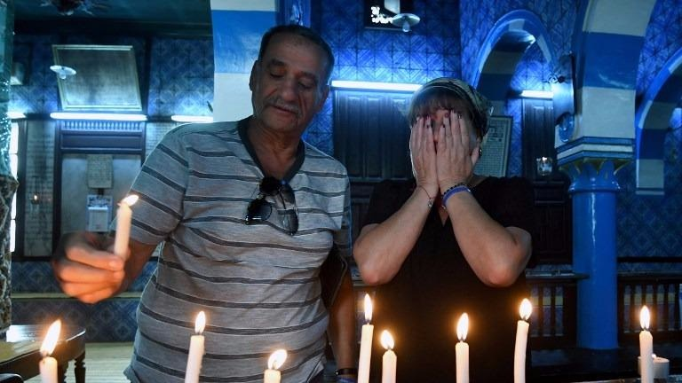 A Tunisian Jewish family lights candles at the Ghriba Synagogue on the Tunisian resort island of Djerba on May 14, 2017 during the second day of the annual Jewish pilgrimage to the synagogue thought to be Africa's oldest. (FETHI BELAID / AFP)