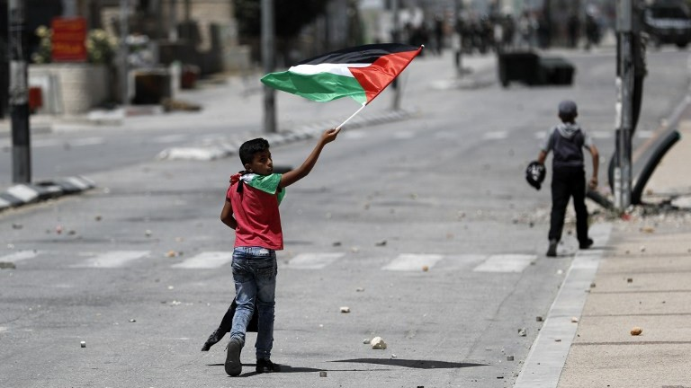 A Palestinian boy waves a Palestinian flag during 'Nakba' Day clashes with Israeli security forces in the West Bank city of Bethlehem on May 15, 2017. (AFP Photo/Thomas Coex)