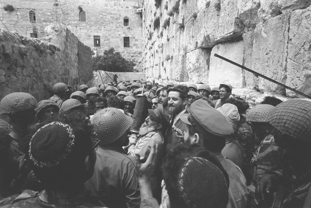 A group of paratroopers surrounds then-IDF chief rabbi Shlomo Goren at the Western Wall on June 7, 1967. (Micha Bar-Am/Defense Ministry's IDF Archive)