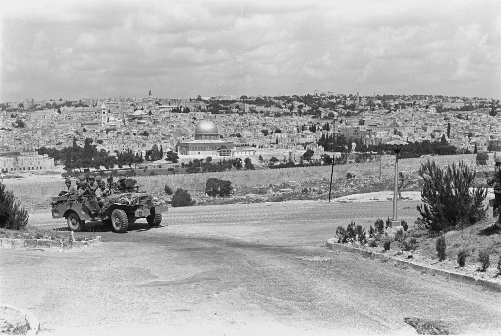 Paratroopers ride in a jeep near the East Jerusalem neighborhood of A-Tur, with the Old City of Jerusalem behind them, on June 5, 1967. (Amos Zucker/Bamahane Magazine/Defense Ministry's IDF Archive)