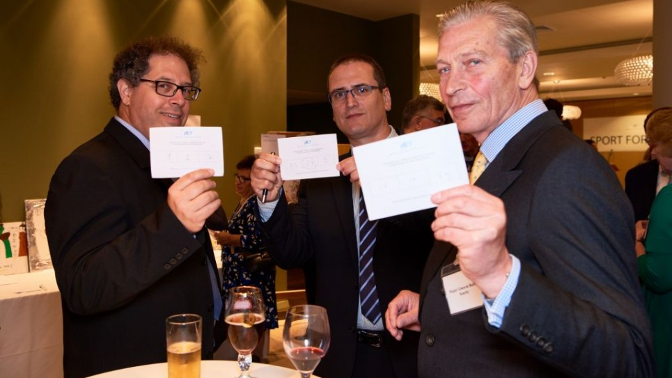 Itay Brafman, Zvi Derin and General Searby with their voting slips for the art exhibition