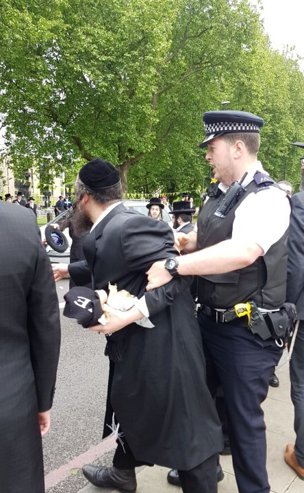 Police detain a member of the hassidic community during scuffles