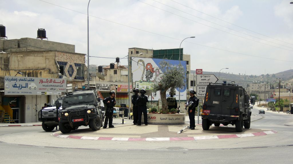 Israel Police officer guard a street where yesterday a group of Palestinians attacked an Israeli settler, who fired back, killing one person and wounding another, in Hawara, in the northern West Bank on May 19, 2017. (Judah Ari Gross/Times of Israel)