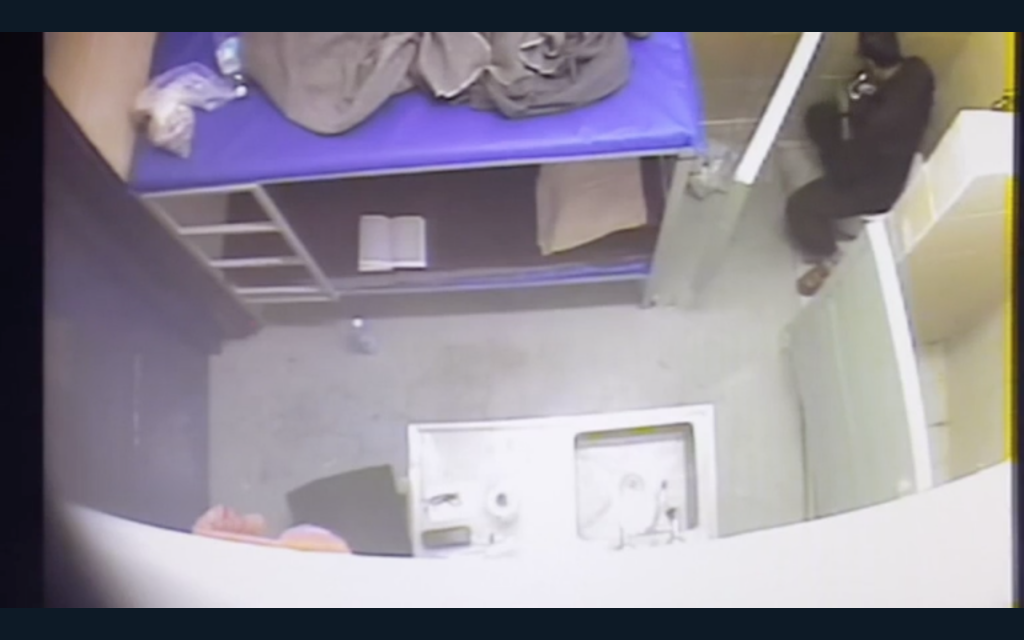 Marwan Barghouti seen in video footage unwrapping a candy bar in his cell while ostensibly leading a hunger strike among Palestinian prisoners. (Screen capture: Israeli Prison Service)