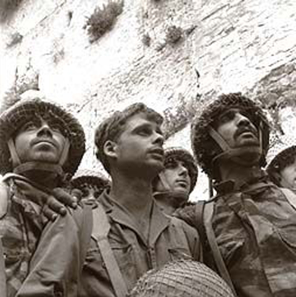 David Rubinger's famed photograph of IDF paratroopers at Jerusalem's Western Wall shortly after its capture. From left to right: Zion Karasenti, Yitzhak Yifat, and Haim Oshri.[a]