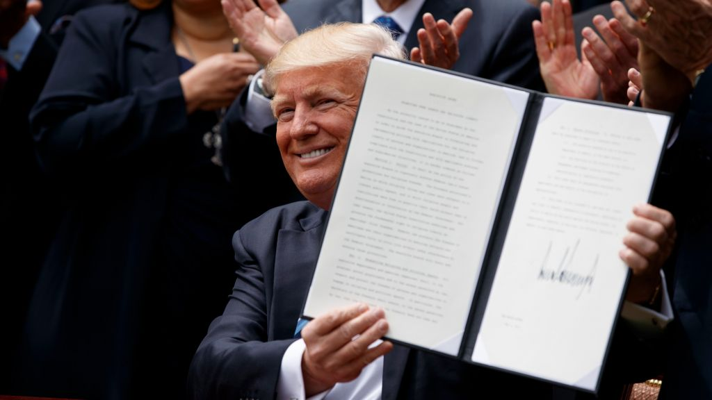 US President Donald Trump holds up a signed executive order aimed at easing an IRS rule limiting political activity for churches Thursday