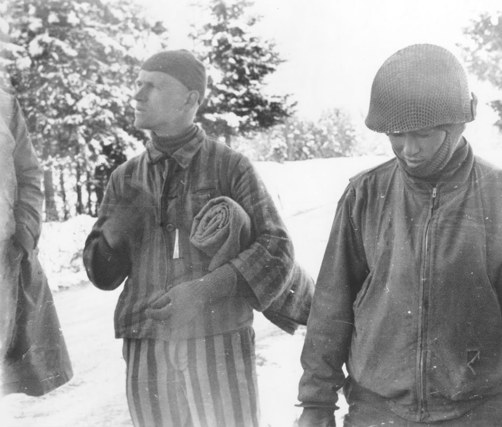 Tahae Sugita (right), a Japanese-American soldier with the 522nd Field Artillery battalion, stands next to a concentration camp survivor he has just liberated on a death march from Dachau. (Courtesy USHMM/Eric Saul)