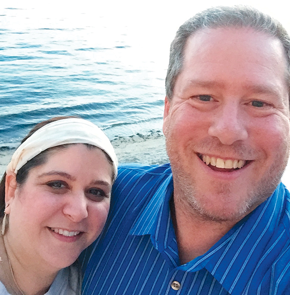 Marcie and Jeff Ingber stand by the sea.