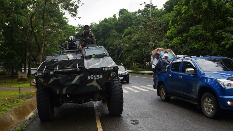 A Philippine soldier sits on an Armoured Personnel Carrier while residents fleeing from Marawi city drive past on a highway going to Marawi in Balo-i town on the southern island of Mindanao