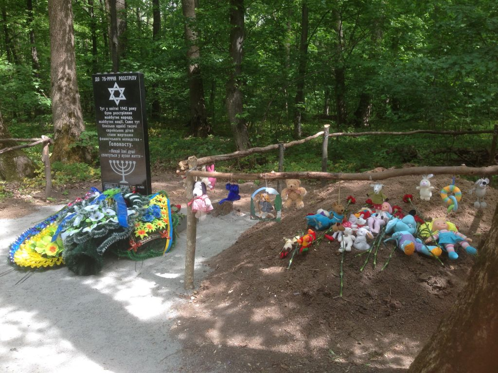 Memorial next to newly-covered over grave of Jewish kids shot by Nazis in 1942. The mass grave was decorated with children's toys for the ceremony on May 9, 2017. (Sue Surkes)