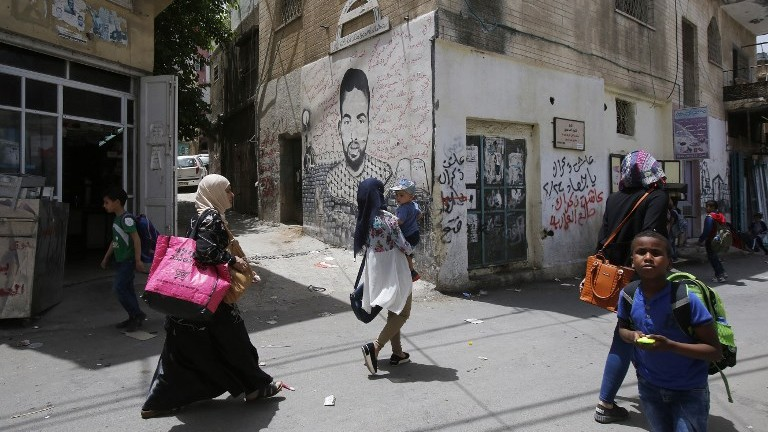 Palestinians walk past graffiti in Deheishe Refugee Camp near the West Bank town of Bethlehem on May 14, 2017. (AFP Photo/Musa Al Shaer)