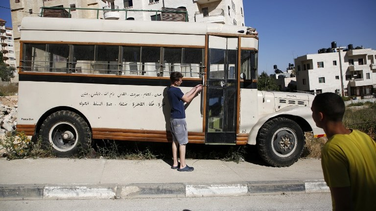 Mohammed Nassar opens the door of a restored pre-1967 bus which bears writing in Arabic of the names of the cities it used to visit, parked on the side of a street in the West Bank city of Ramallah on May 31, 2017. (AFP Photo/Abbas Momani)