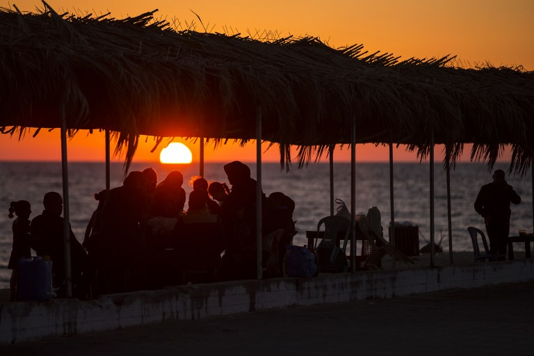 Palestinian families gather at the beach, during power cuts, to break their fast in Gaza City on May 31, 2017, during the Muslim Holy month of Ramadan. (AFP PHOTO / MAHMUD HAMS)