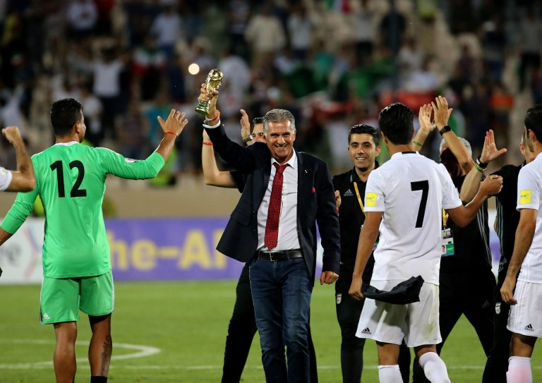 Portuguese coach Carlos Queiroz of the Iranian national football team celebrates with players after winning the 2018 World Cup qualifying football match between Iran and Uzbekistan at the Azadi Stadium in Tehran on June 12, 2017. (AFP PHOTO / ATTA KENARE)
