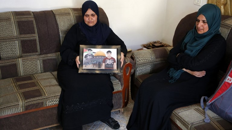 The mother of Usama Atta holds up his picture at their home in the village of Deir Abu-Mashal near the West Bank city of Ramallah, on June 17, 2017, the day after he and two other Palestinians stabbed to death an Israeli policewoman and wounded four other people in a terror attack near Damascus Gate in Jerusalem. (AFP PHOTO / ABBAS MOMANI)