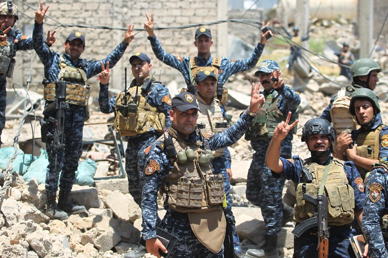 Iraqi forces gesture during their advance towards Mosul's Old City on June 18, 2017, during the ongoing offensive by Iraqi forces to retake the last district still held by the Islamic State group. (AFP PHOTO / AHMAD AL-RUBAYE)