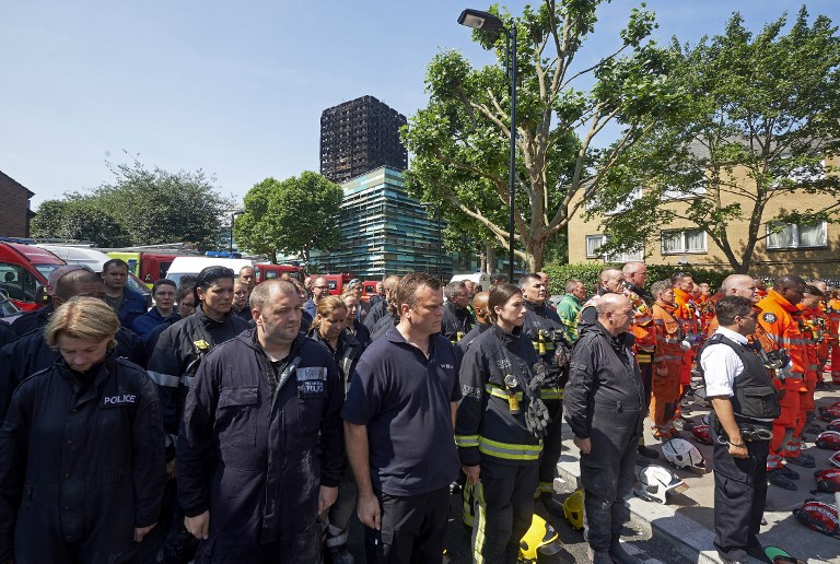 Members of London's emergency services observe a minutes' silence in memory of the victims of the June 14 fire at the Grenfell Tower block, pictured on the horizon, in Kensington, west London, on June 19, 2017. (AFP PHOTO / NIKLAS HALLE'N)