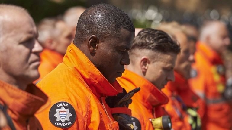 Members of London's emergency services observe a minutes' silence in memory of the victims of the June 14 fire at the Grenfell Tower block, pictured on the horizon, in Kensington, west London, on June 19, 2017. (NIKLAS HALLE'N / AFP)