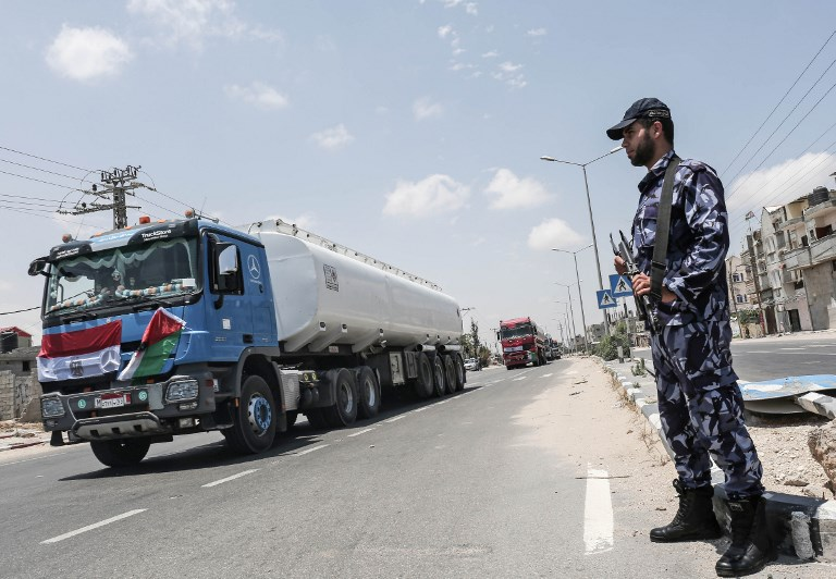 Palestinian security forces stand guard as Egyptian trucks carrying fuel drive down a street after entering the southern Gaza Strip from Egypt through the Rafah border crossing on June 21, 2017. (AFP Photo/Said Khatib)