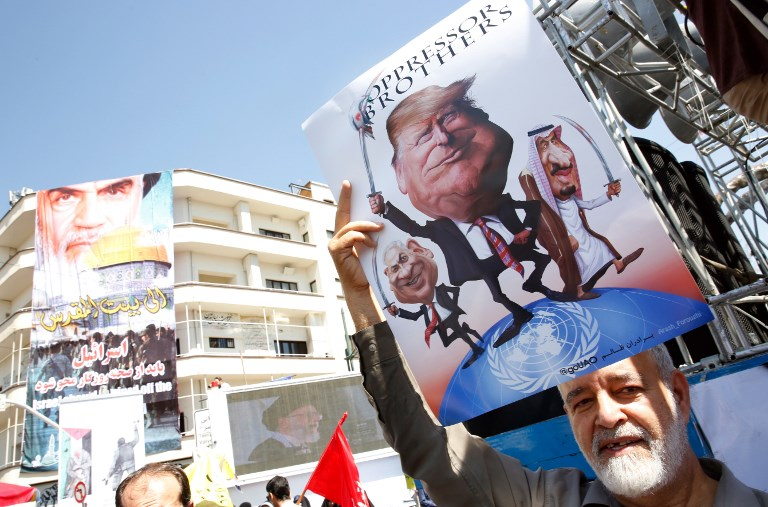 An Iranian man holds a poster bearing images of Israeli Prime Minister Benjamin Netanyahu, US President Donald Trump and Saudi King Salam during a parade marking al-Quds (Jerusalem) day in Tehran on June 23, 2017. (AFP PHOTO / STRINGER)
