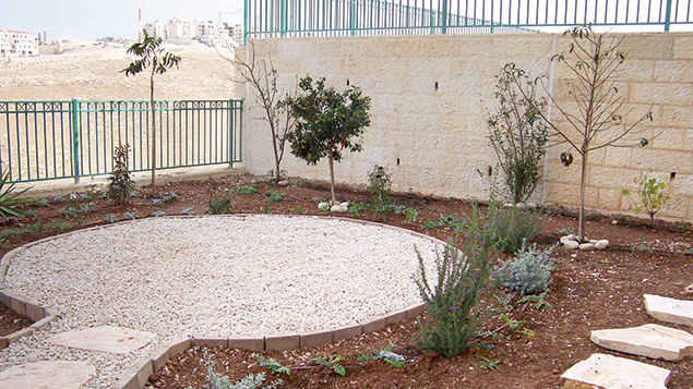 A sitting area designed by Shmulik is set off by white pebbles.