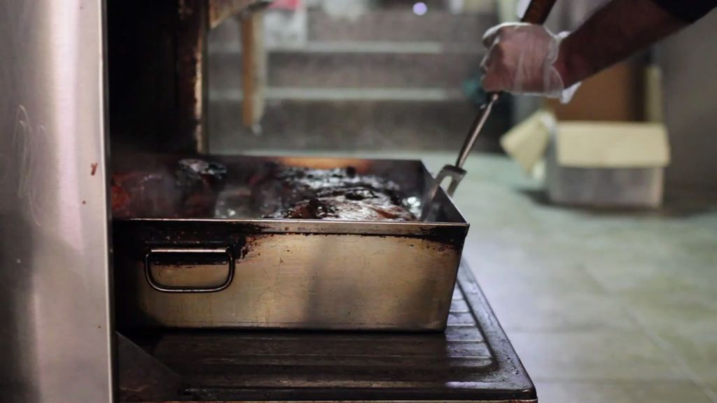 Pulling fresh braised brisket out of the oven at David's Brisket House in Brooklyn, New York. (YouTube Screenshot)