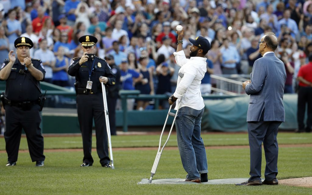 Injured Capitol Hill Police officer David Bailey throws out a ceremonial first pitch with Joe Torre MLB's Chief Baseball Officer before the annual congressional baseball game