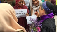 Rabbi Laura Janner-Klausner talking to Muslim women, holding signs that say 'Not in our Name'