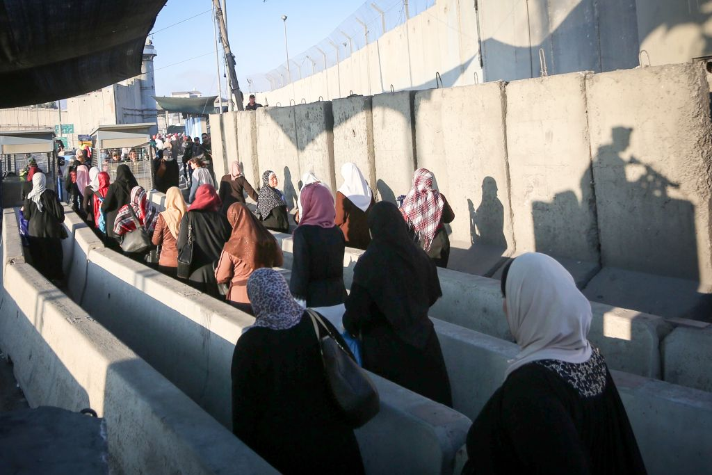 Palestinians cross the Qalandiya checkpoint, outside of the West bank city of Ramallah, as they head to the Al-Aqsa mosque compound in Jerusalem's Old City to attend the first Friday prayers of Ramadan. June 2, 2017. (FLASH90)