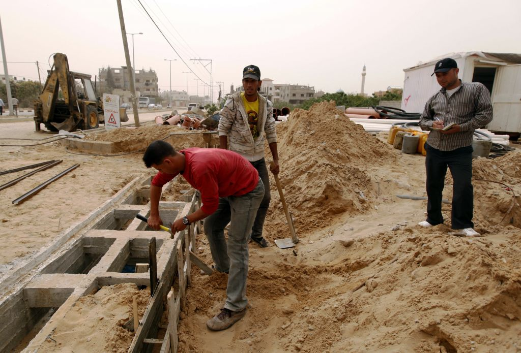 In this April 8, 2013 photo, Palestinians work on a Qatar-funded road in Gaza City. (AP Photo/ Hatem Moussa)