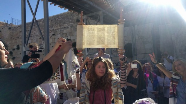 A young member of Women of the Wall holds up the miniature Torah scroll during the monthly Rosh Hodesh service on June 25, 2017, in the women's section of the Western Wall plaza. (Melanie Lidman/Times of Israel)