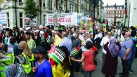 Pro-Palestinian supporters wave the Hezbollah flag, which features a rifle, on their march through central London