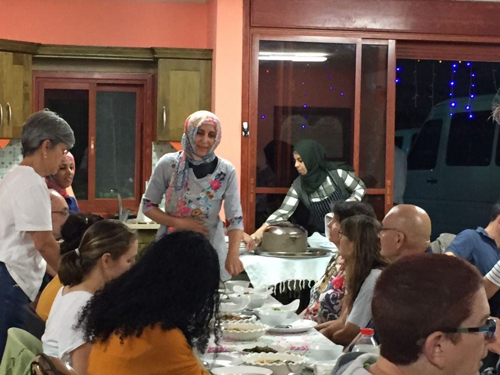 Proprietress of an in-house restaurant Manal Karaman describes to participants of the Umm Al-Fahm Ramadan Nights tour what food she has prepared for their break-fast meal, June 22, 2017. (Amanda Borschel-Dan/Times of Israel)