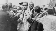 Pressman, center right, side to the camera, in front of Malcolm X at a 1964 press conference