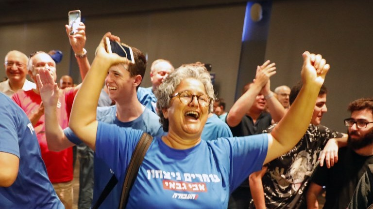 Supporters of Avi Gabbay celebrate in Tel Aviv after he was elected leader of the Labor party on July 10, 2017. (AFP Photo/Jack Guez)