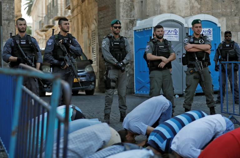 Israeli security forces stand guard in front of Palestinian Muslim worshipers praying outside Lions Gate a main entrance to the Temple Mount compound in Jerusalem's Old City