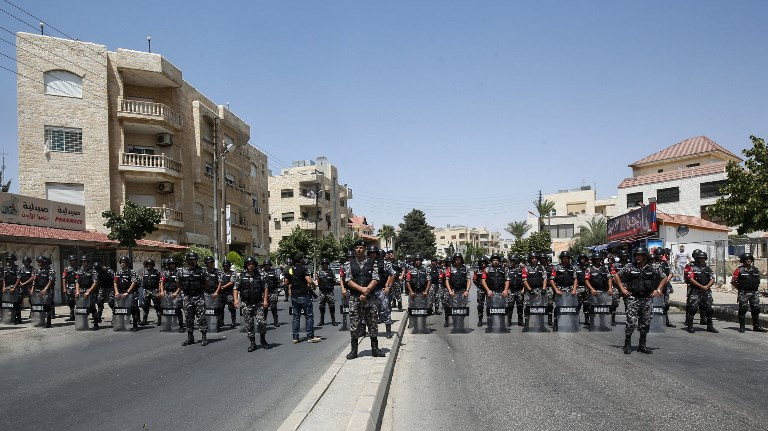 Jordanian security forces stand on guard in front of protesters during a demonstration near the Israeli embassy in the capital Amman on July 28, 2017, calling for the shutting down of the embassy, expelling the ambassador, and canceling the 1994 peace treaty with Israel. (AFP PHOTO / KHALIL MAZRAAWI)