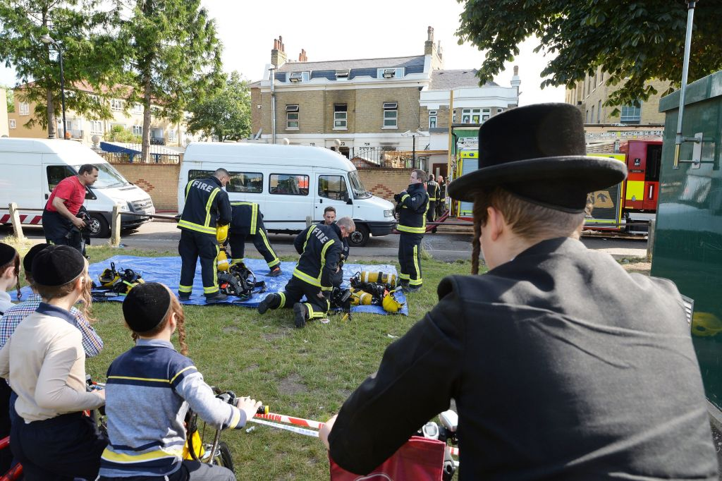 Jewish members of the public watch firefighters outside a school in Craven Walk in Hackney, east London, after a fire broke out shortly before midnight on Tuesday. Photo credit: John Stillwell/PA Wire