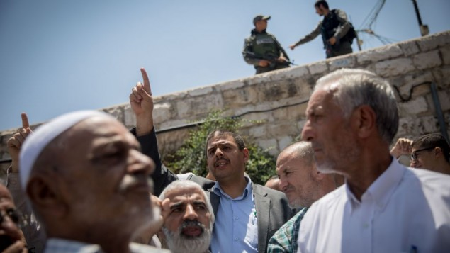 Palestinians pray as Israeli policemen guard during Friday prayers in the East Jerusalem neighbourhood of Wadi al-Joz. Israeli police blocked the entrance to the Al aqsa mosque compound on Friday following the terror attack earlier today.   Photo by: JINIPIX