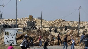Palestinian protesters clash with Israeli soldiers ,while an army bulldozer closes the main road with dirt during their operation to search and measure the family house of Omar al-Abed, 20, the terrorist who perpetrated Friday's attack at the West Bank settlement of Halamish, in preparation for demolition, in the West Bank village of Kobar, near Ramallah, July 22, 2017. (AP Photo/Nasser Nasser)