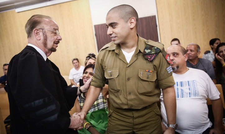 Elor Azaria (center) shakes hands with his attorney Yoram Sheftel before the start of a court hearing at the IDF's Tel Aviv headquarters on July 17, 2017. (Miriam Alster/Flash90)
