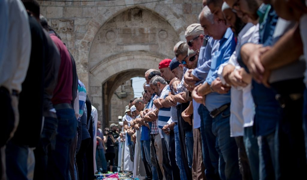 Muslim worshipers perform noon prayers at the Lions Gate, outside the Temple Mount, in Jerusalem's Old City on July 19, 2017. (Yonatan Sindel/Flash90)
