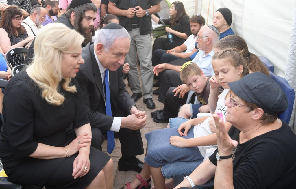 Prime Minister Benjamin Netanyahu and his wife Sara console relatives of the three members of the Salomon family who were killed in a terror attack in Halamish on July 22, 2017. (Amos Ben Gershom/GPO)