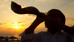 A young Jewish boy blows the shofar horn