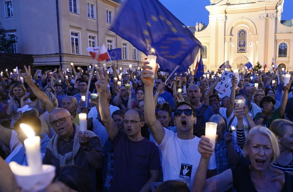 Anti-government protesters raise candles and shout slogans, as they gather in front of the Supreme Court in Warsaw, Poland, Saturday, July 22, 2017 (AP Photo/Alik Keplicz)