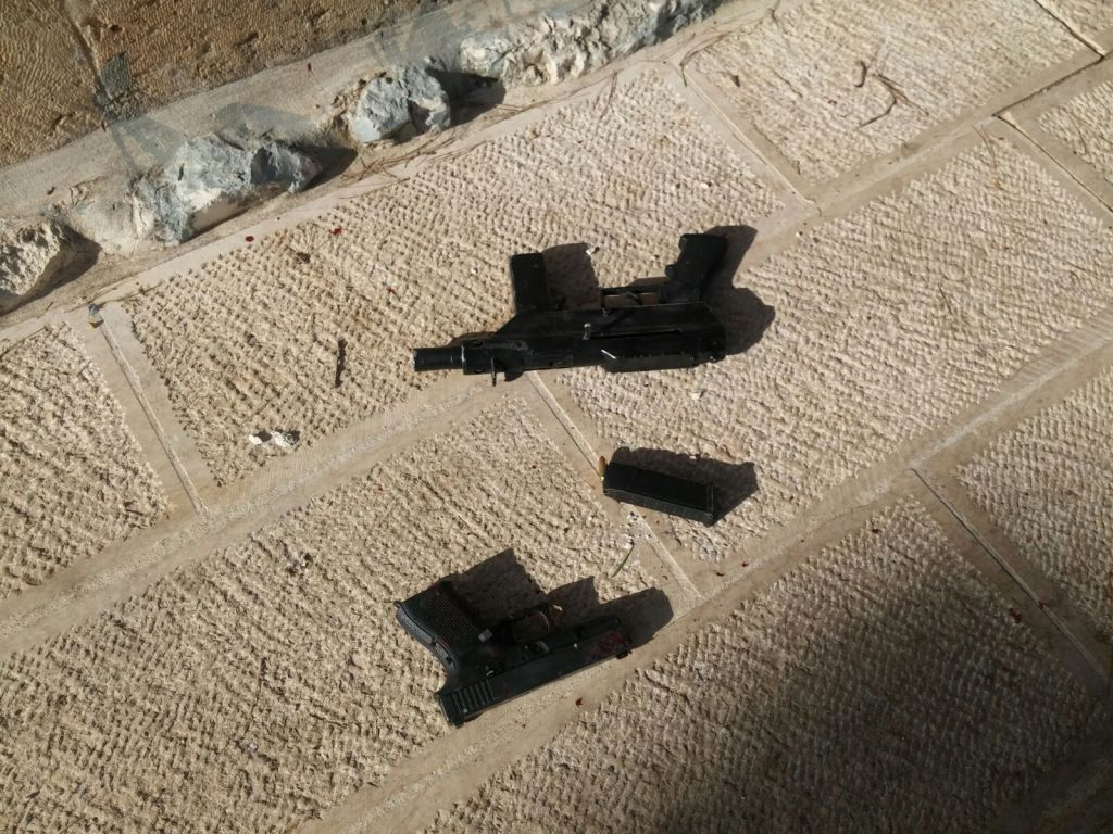 A pistol and one of two Carlo-style submachine guns used in a shooting attack that left two Israeli seriously wounded near the Temple Mount in Jerusalem's Old City