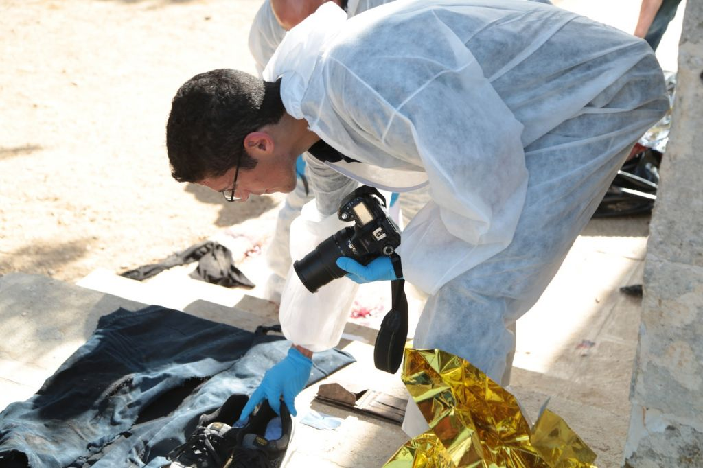 Crime scene investigators collect evidence from the scene of a shooting attack near the Temple Mount complex in the Old City of Jerusalem on July 14, 2017. (Israel Police)