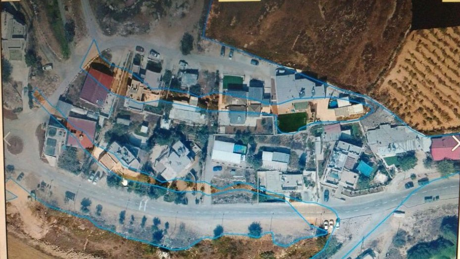 An aerial photograph of the Netiv Ha'avot outpost. The areas colored in blue were deemed by the High Court to be state land. The 17 structures that stand on the non-shaded areas have been sanctioned for demolishment. (Courtesy)